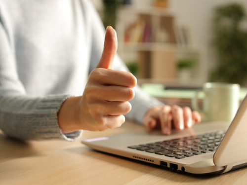 Woman hands with thumbs up using laptop at night