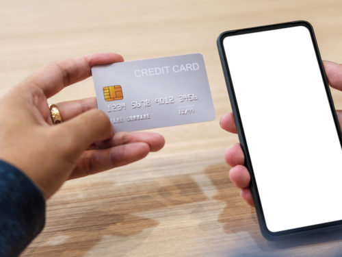 Close up hand of woman shopping online with credit card using smart phone at cafe